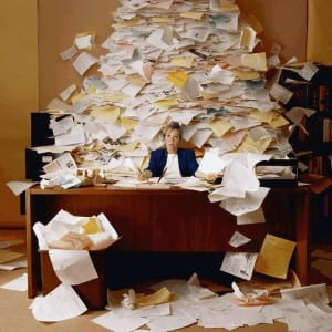 Woman sat behind desk with a mountain of paper on it.