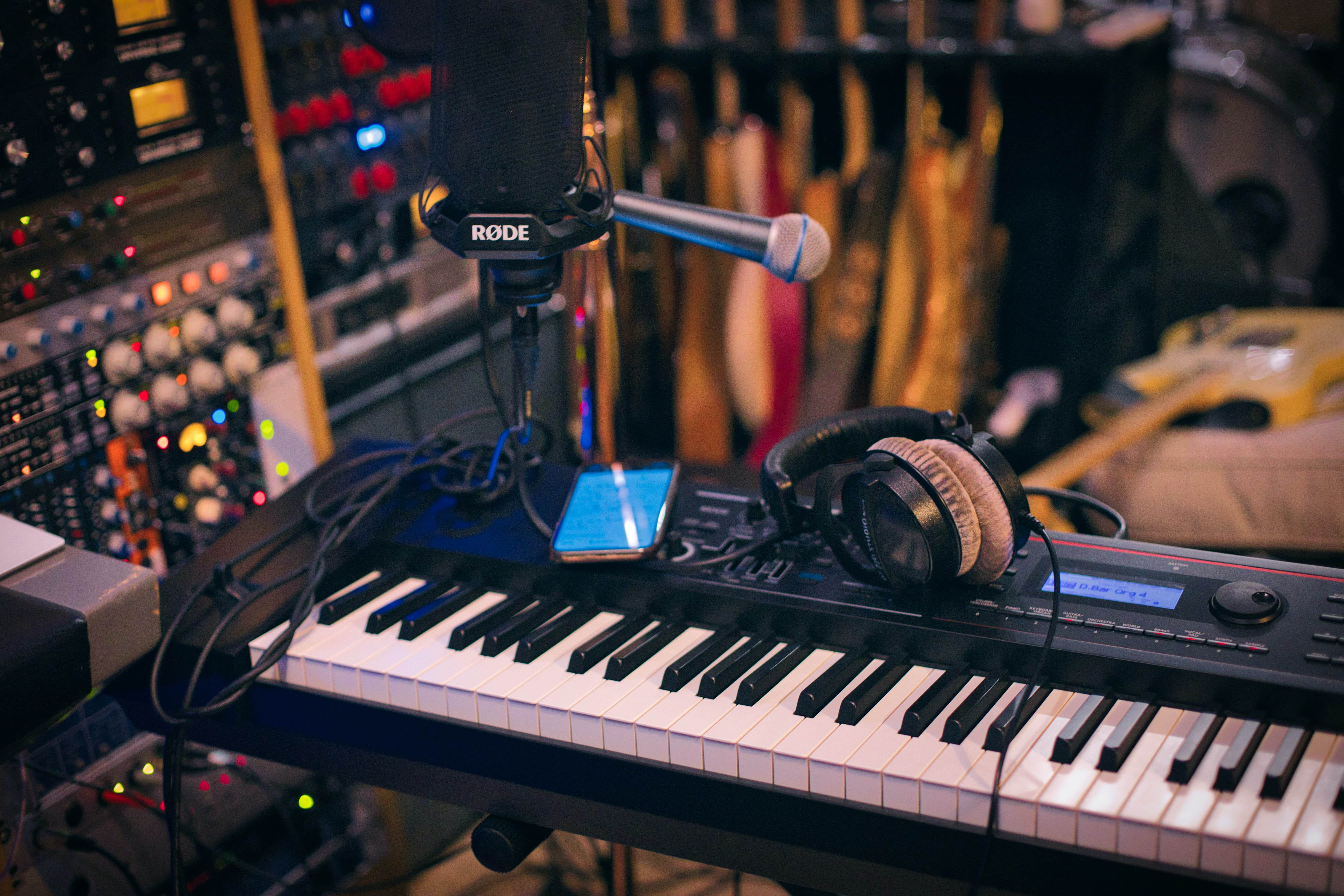 small microphone stand positioned on keyboard with music production equipment in background