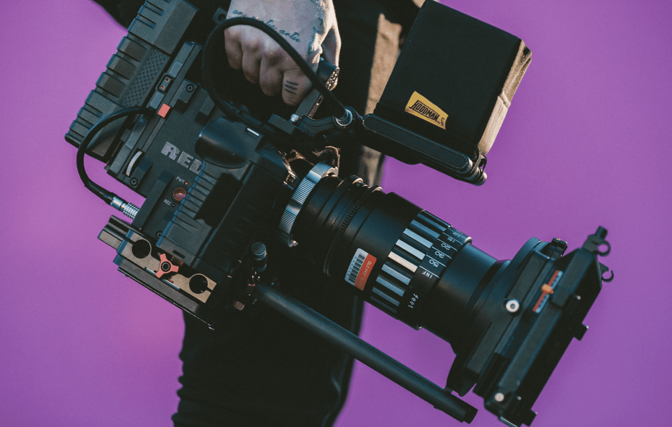 man holding video camera in front of purple background