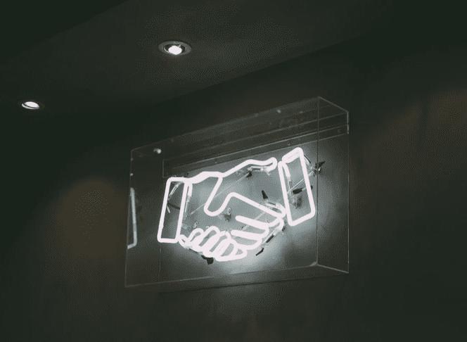 lit up sign of shaking hands seen on dark background