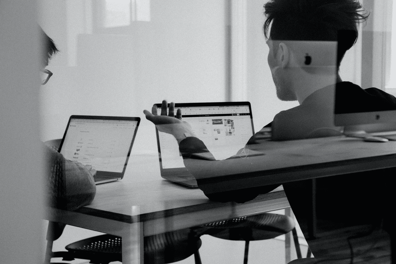 group in meeting with laptops in front of them reviewing status of a freelancer