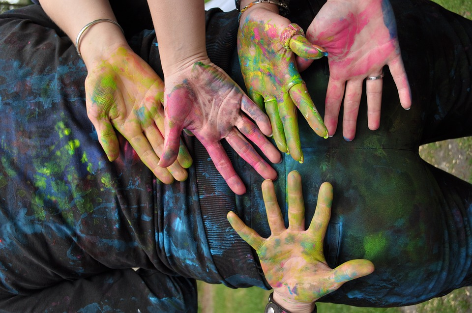 Photograph of 5 hands, all covered in paint. With creative agencies, too many differing opinions can impact on the quality of the final work.
