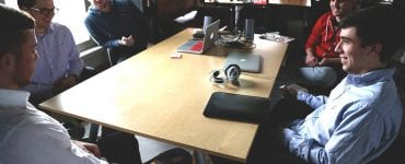 Photograph of creative agency staff around a table in a meeting. This article explains why agencies can often fail to deliver high quality content.