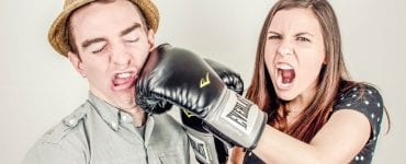 Woman with boxing gloves punching a man in a hat. This article explains why hiring your friends for freelance work can often be a bad idea.
