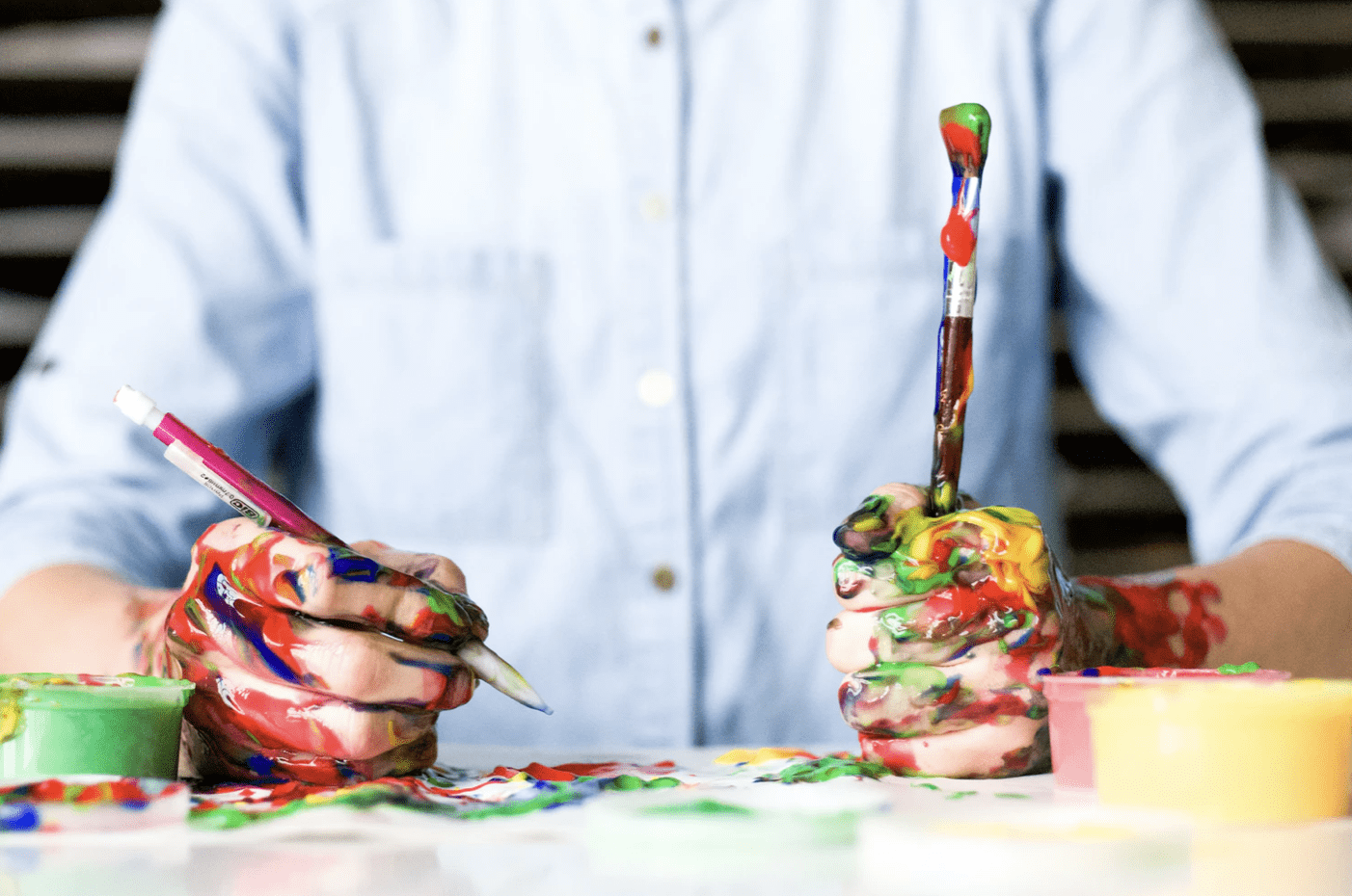 planning creative content, man holding a paintbrush in one hand and pencil in the other with paint all over desktop