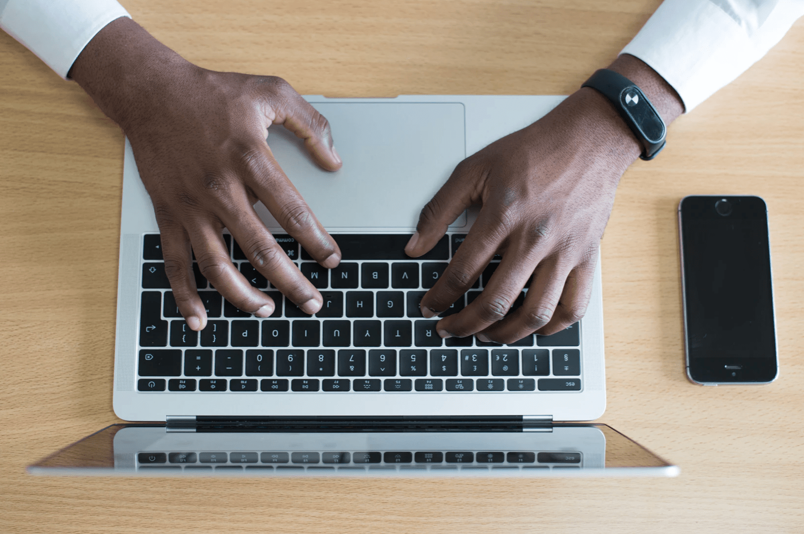 man typing on keyboard laptop with professional looking watch on his wrist