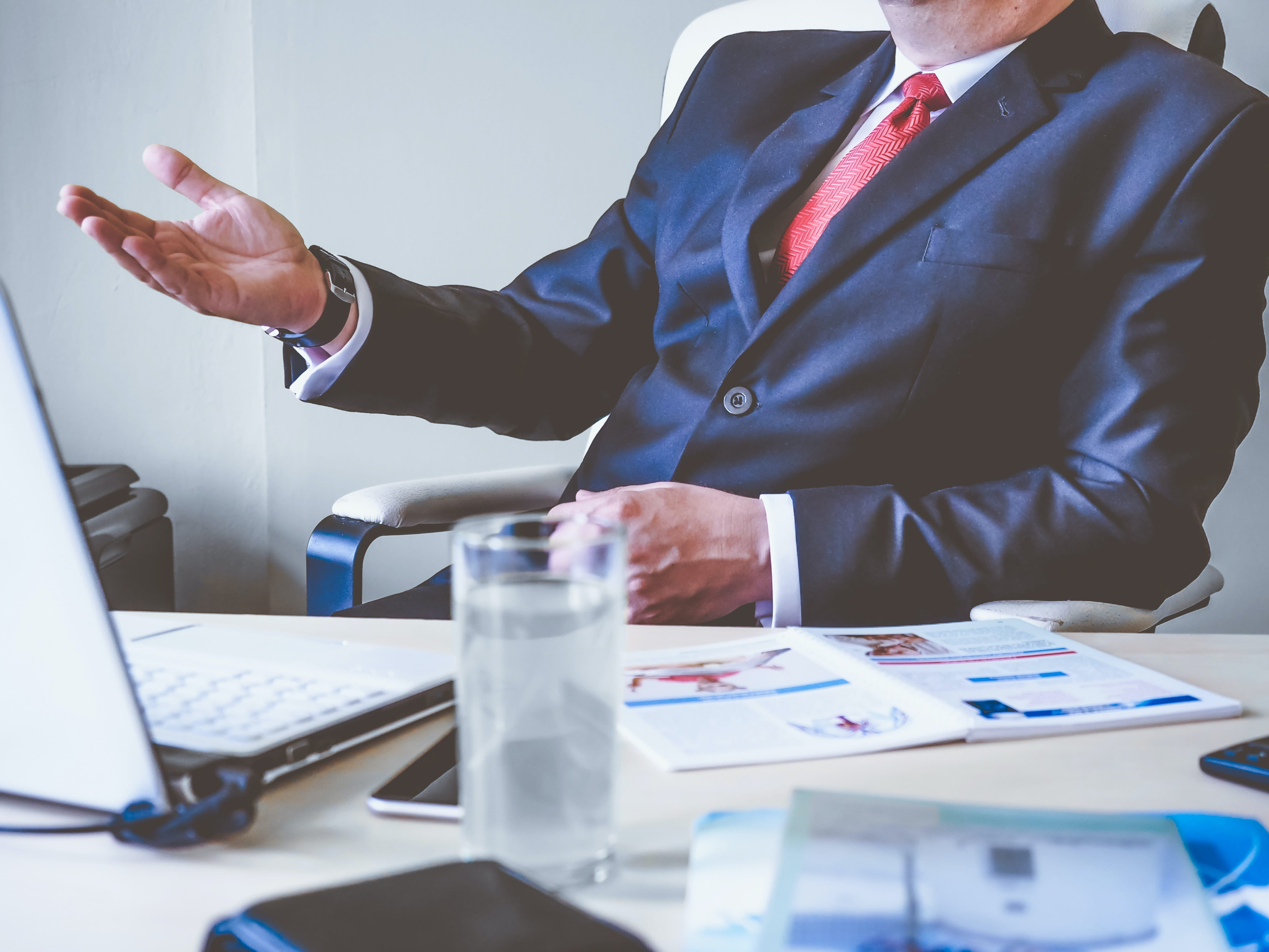 man in suit raising right hand in office environment