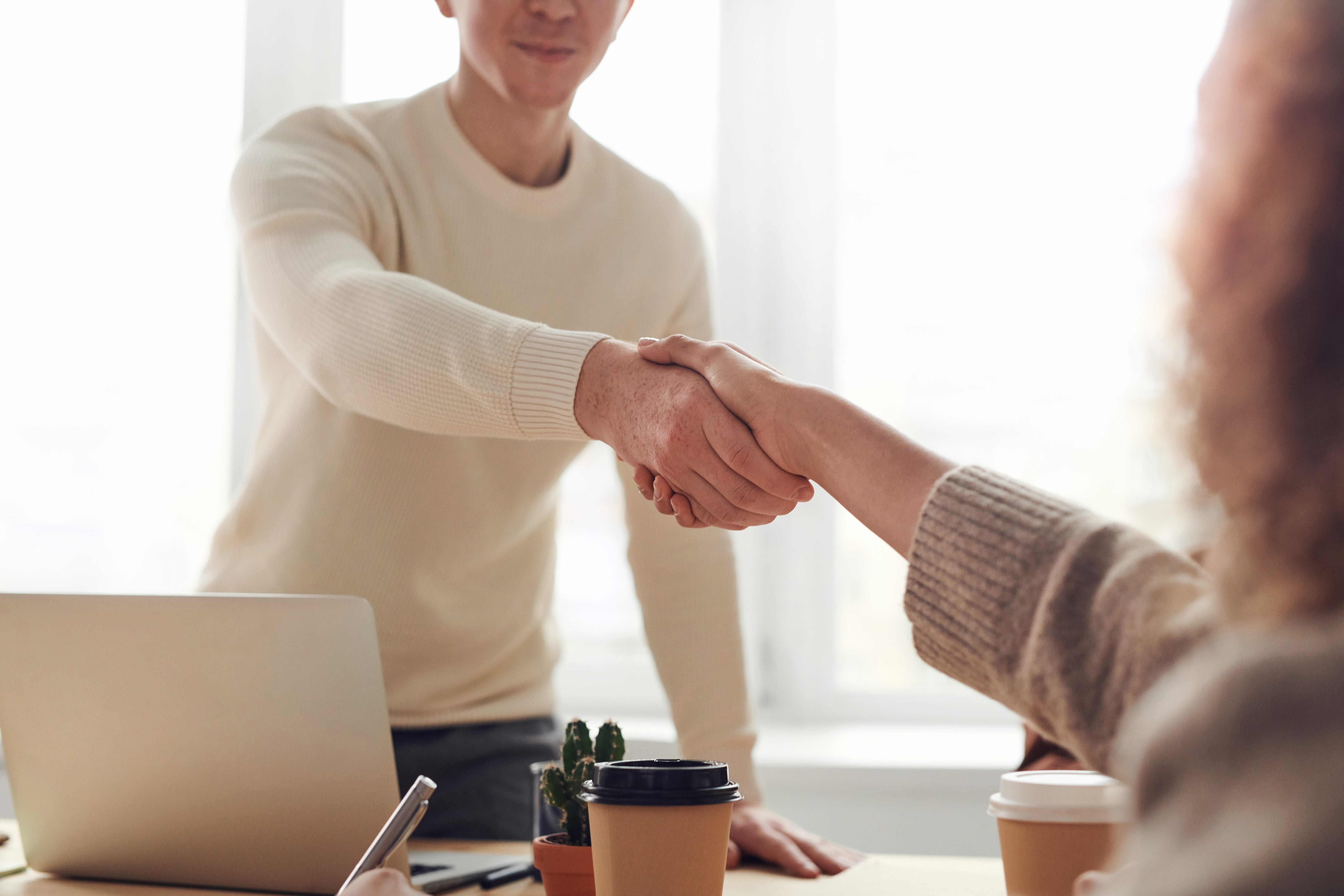man shaking hands with woman in office setting