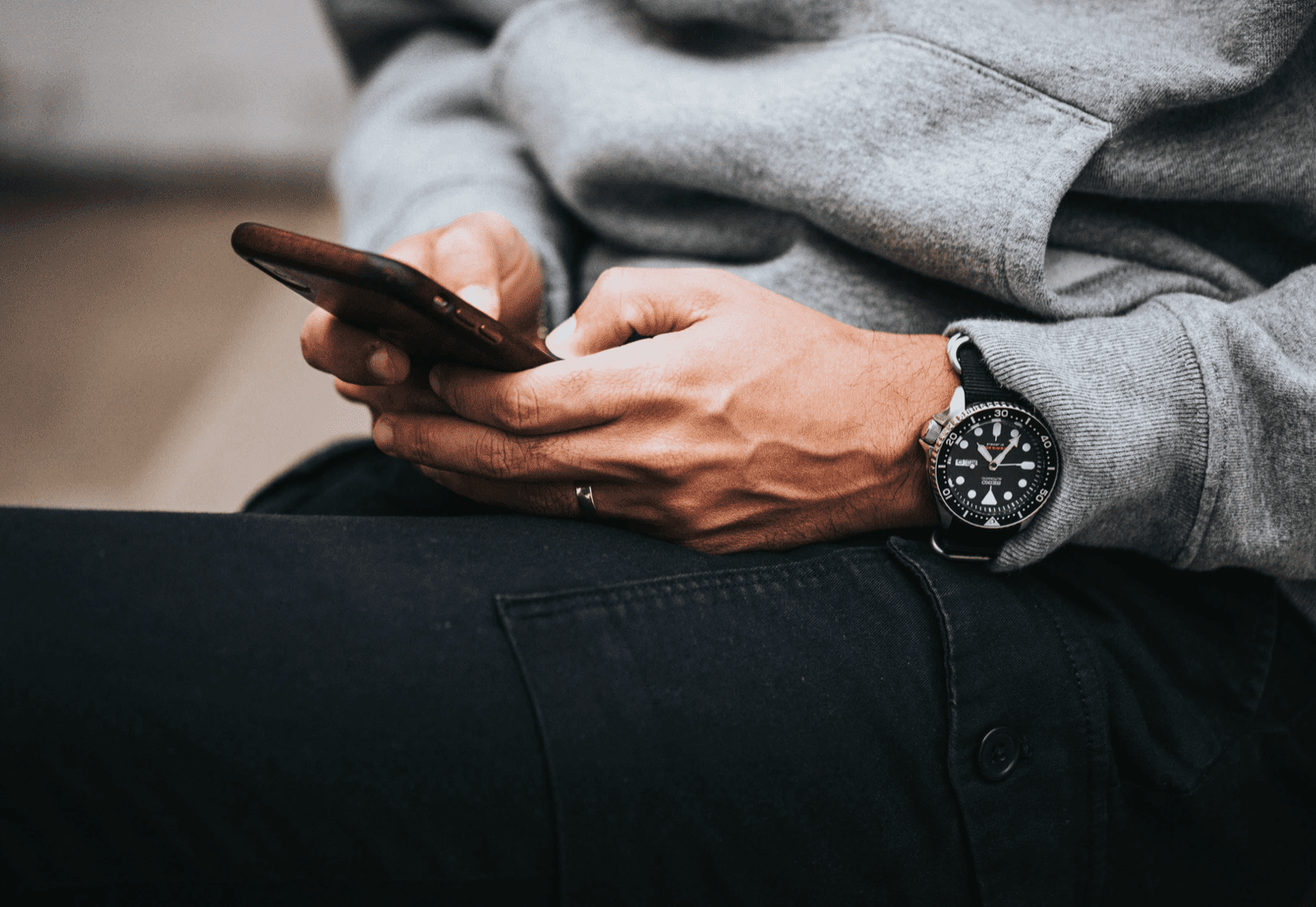 man wearing expensive watch looking down at phone