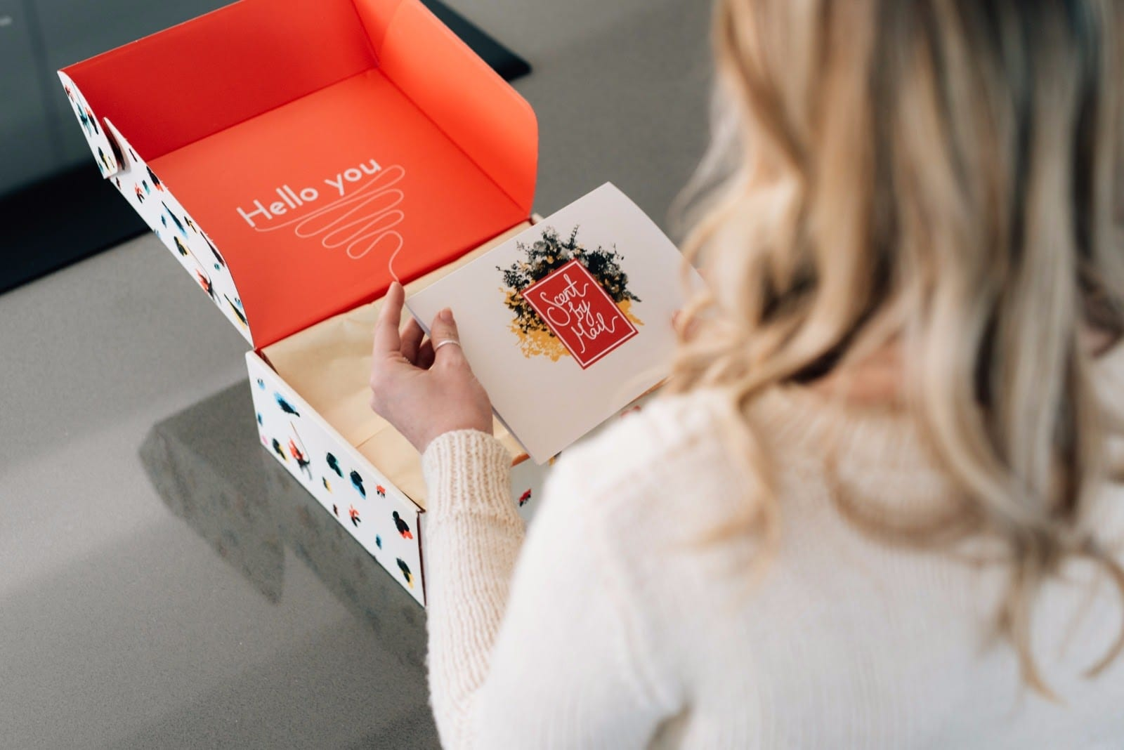 woman reading a Christmas card from a branded box pr package