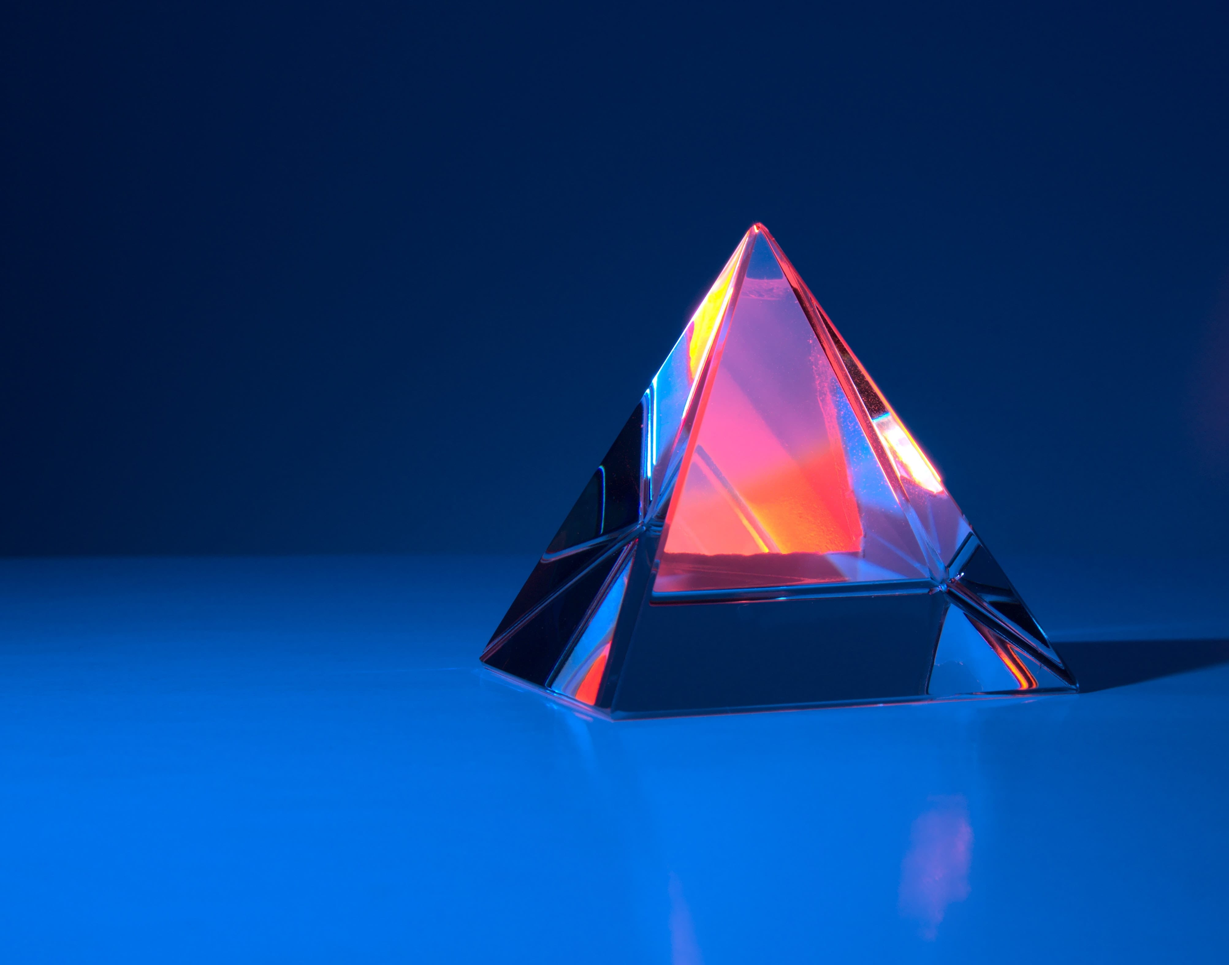 graphic design of pyramid with orange and yellow colours on blue background