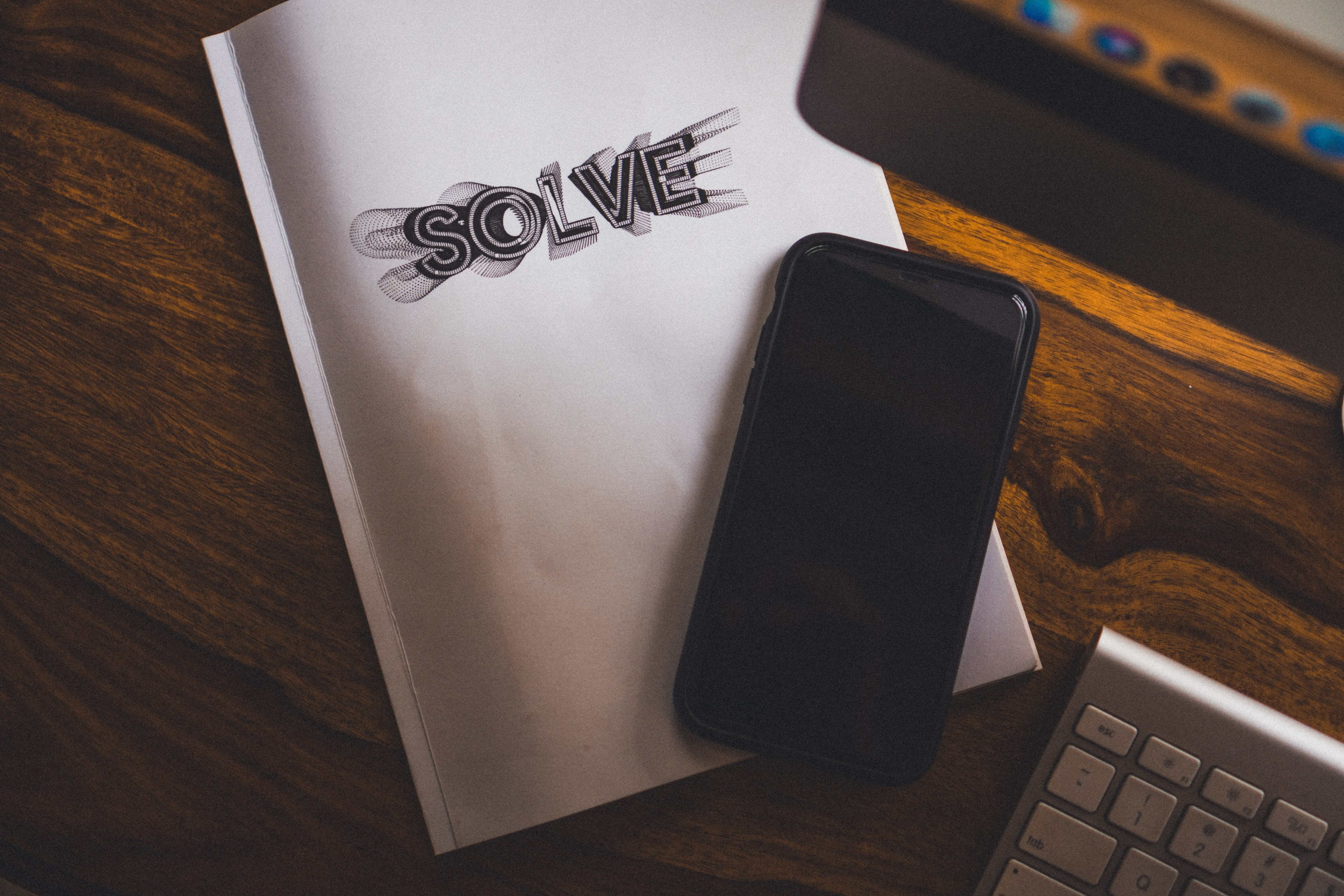 phone resting on notepad with 'solve' written across it