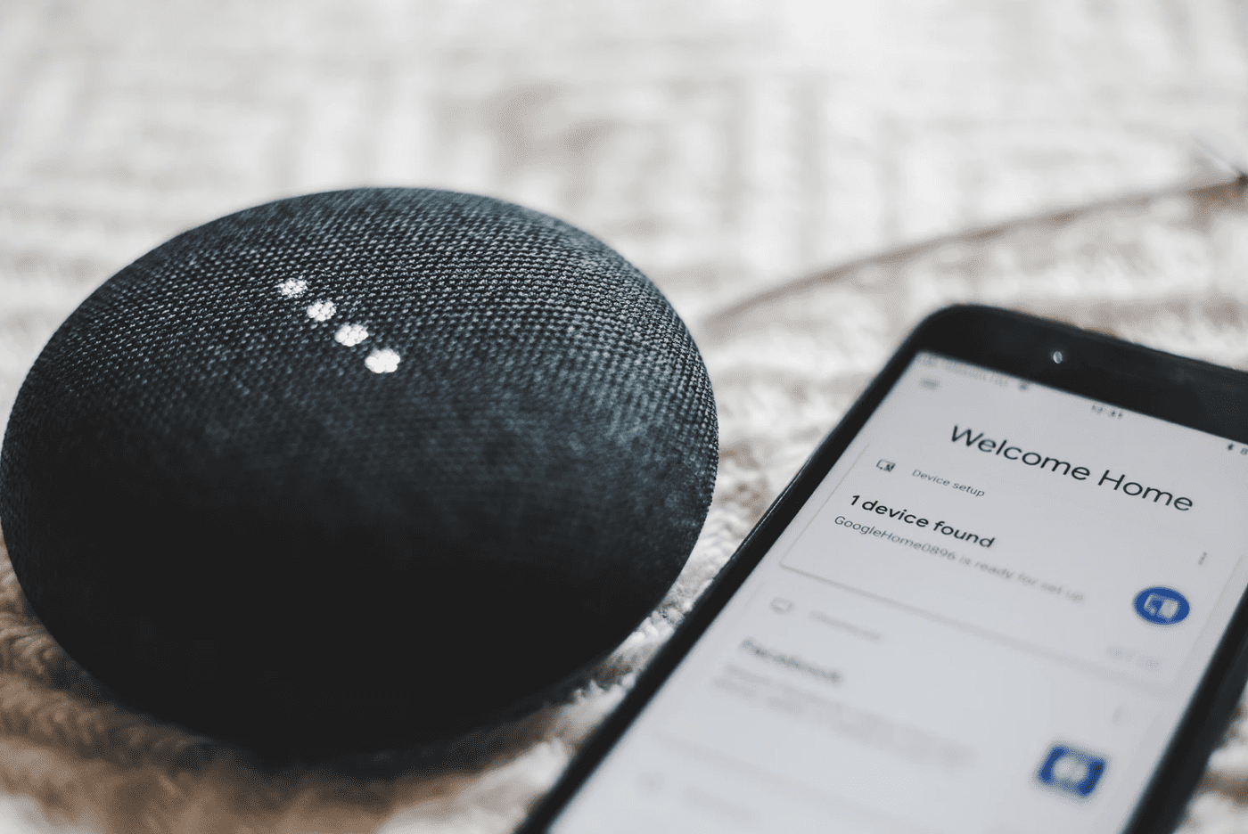voice assistant app web technologies open on phone with voice assistant product beside it
