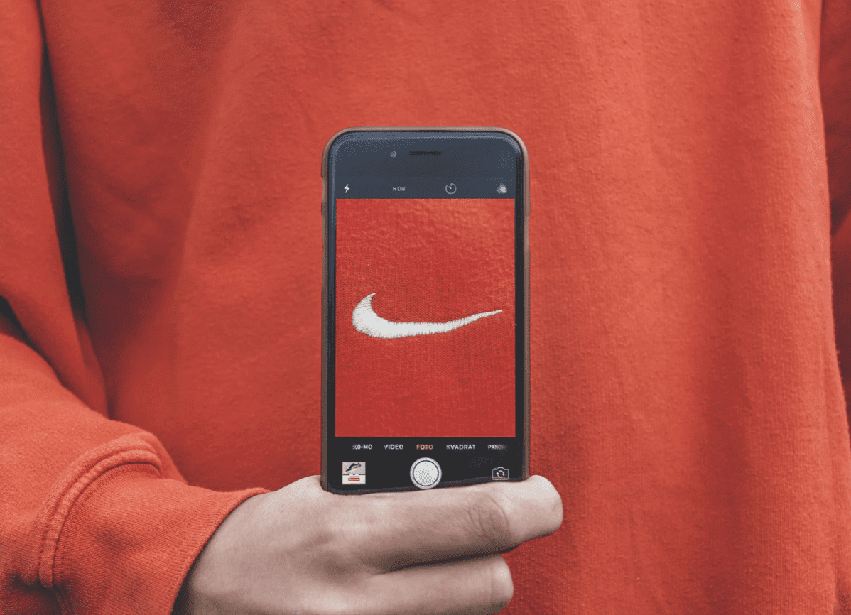 a nike symbol seen on a phone which is being held infront of a man wearing a jumper