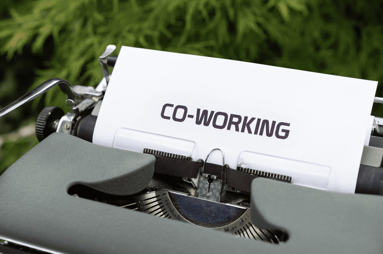 a typewriter with the words 'co-working' printed onto its paper