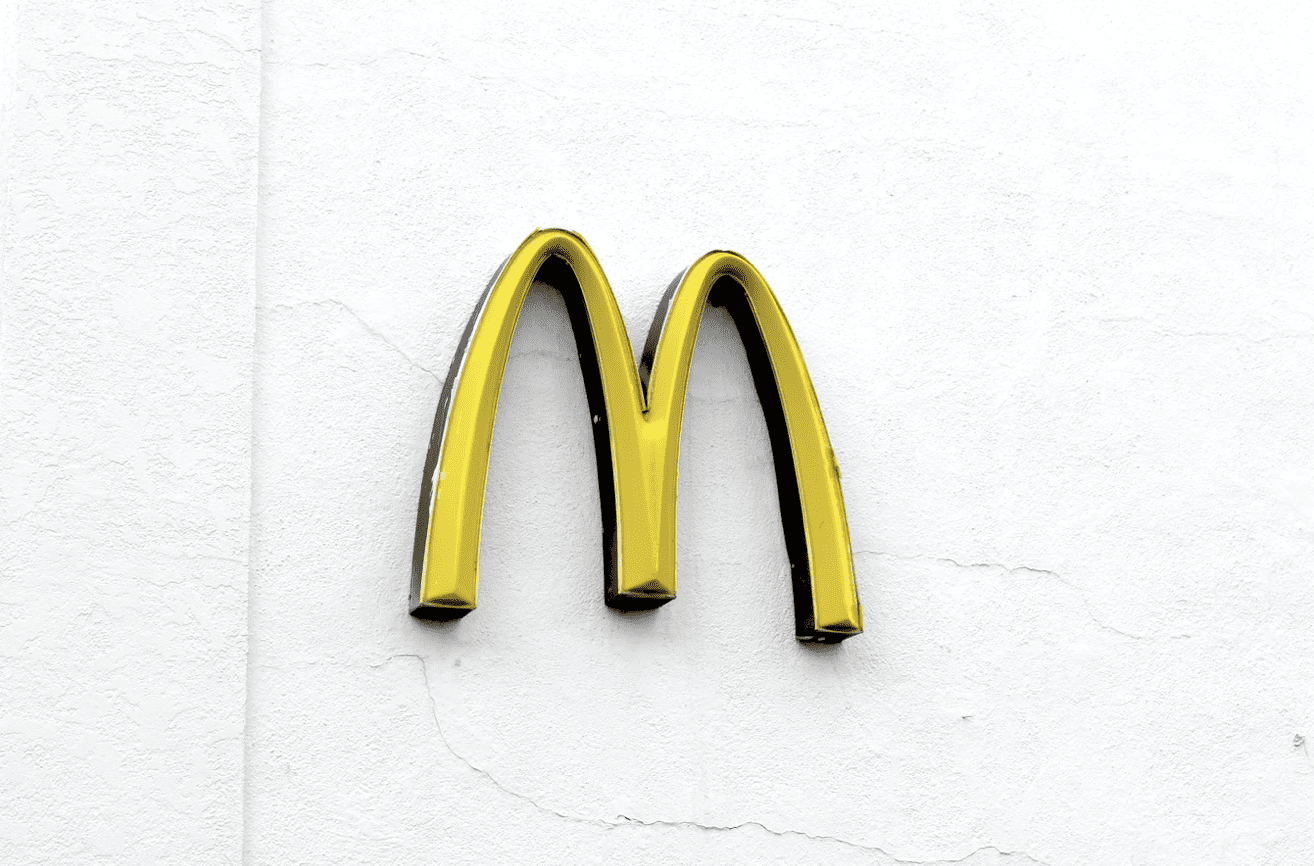 a McDonalds logo seen on the side of a white plastered wall