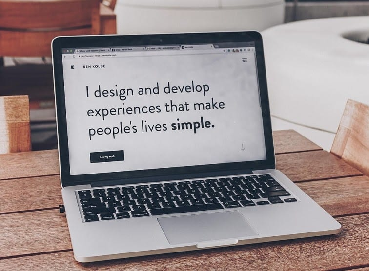 laptop screen displaying web technologies, reads 'I design and develop experiences that make people's lives simple'