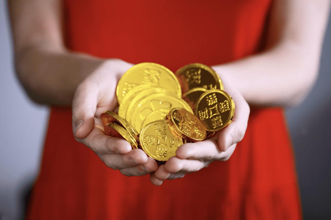 scam designer holding a pile of coins