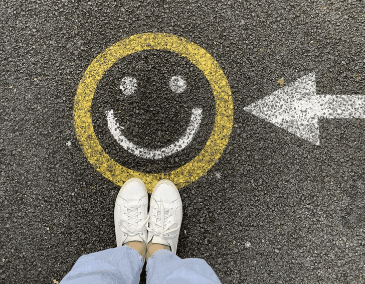 smiley face painted on ground with person standing infront of it