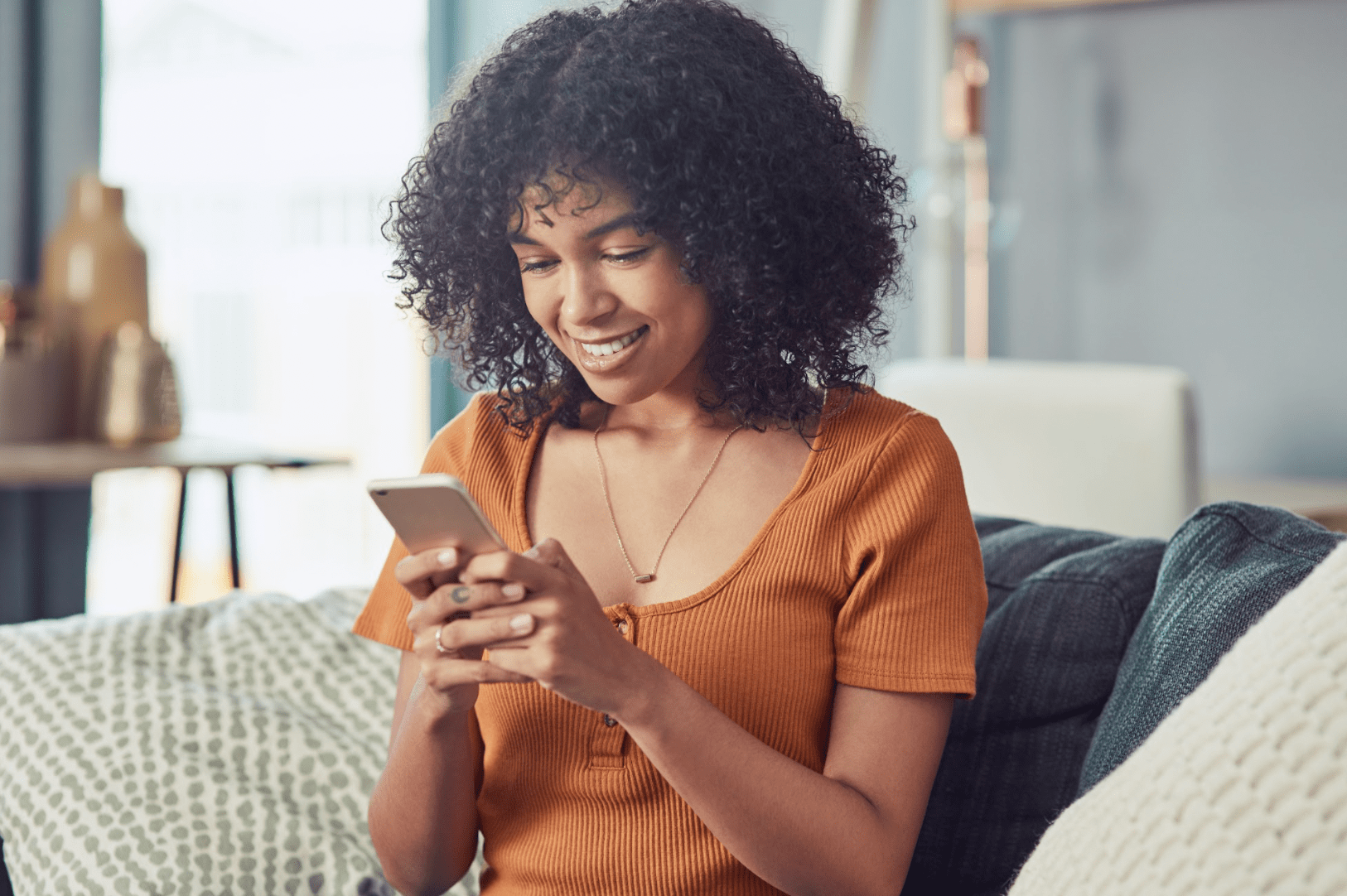 woman looking down at phone and smiling
