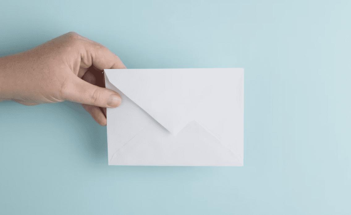 hand holding a white envelope